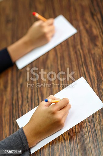 820495452 istock photo Writing hands on a desk in classroom 1073672146