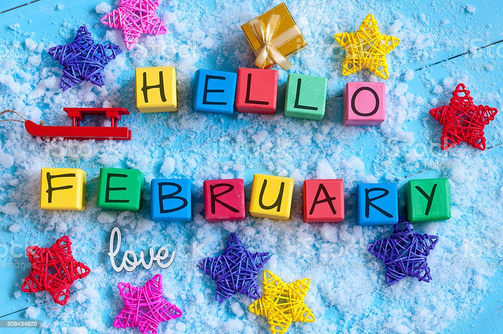writing hello february on toy wooden colour cubes with decor stock photo