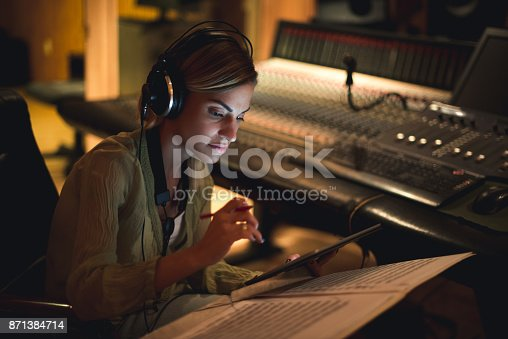 Young musician writing her next song in a music studio.