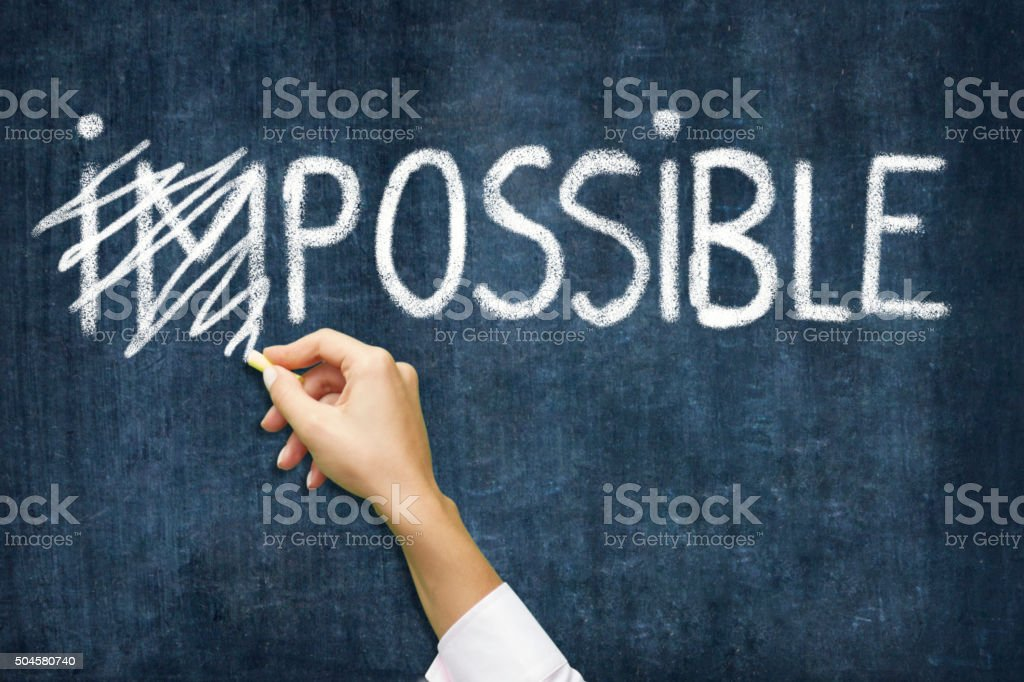 Writing Impossible to Possible  on blackboard stock photo