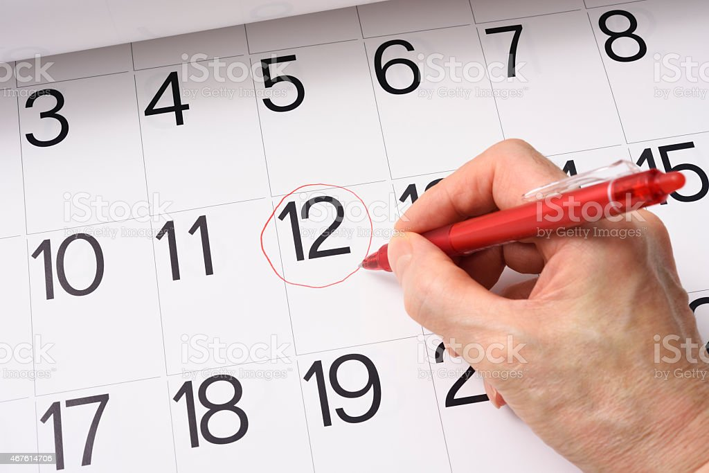 Close-up of writing in a red round mark on the calendar.