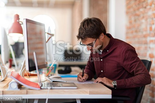Young man sitting in front of the computer at his workplace