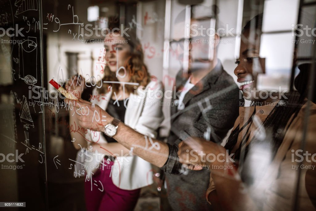 Writing Mathematical Formulas On Transparent Wipe Board stock photo