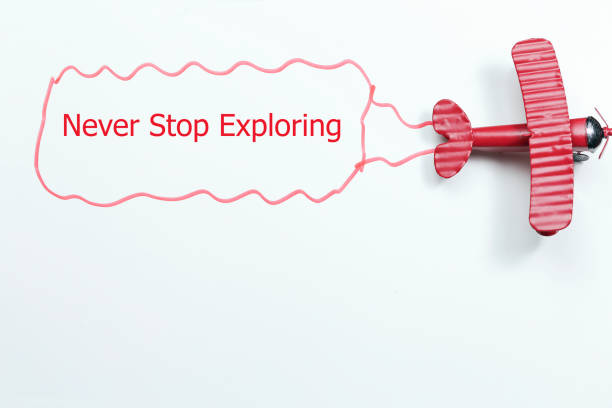 writing never stop exploring red toy airplane with talk bubble on white background writing never stop exploring red toy airplane with talk bubble on white background descry stock pictures, royalty-free photos & images