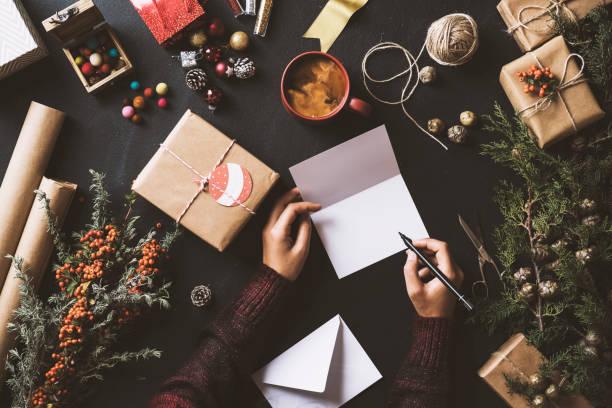 writing new year christmas cards, table top flat lay - weihnachtskarte stock-fotos und bilder