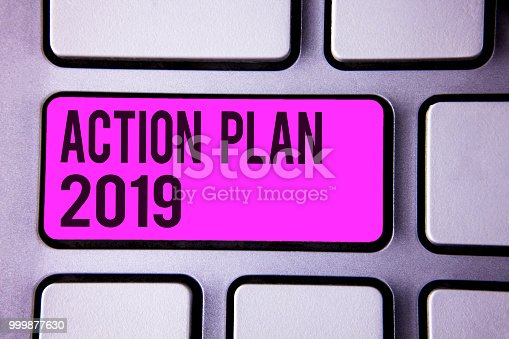 istock Writing note showing  Action Plan 2019. Business photo showcasing Challenge Ideas Goals for New Year Motivation to Start Keyboard purple key black letters words Intention text on computer. 999877630