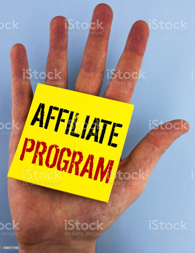 Writing note showing  Affiliate Program. Business photo showcasing software link songs apps books and sell them to earn money written on Sticky Note Paper on the plain blue background Hand. stock photo