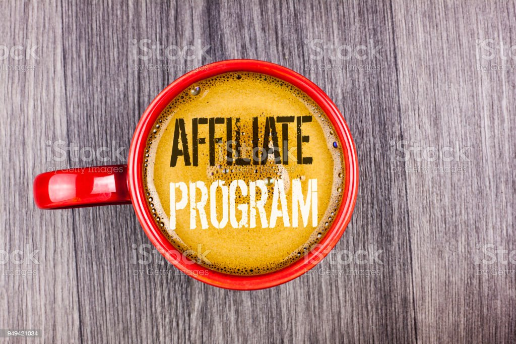Writing note showing  Affiliate Program. Business photo showcasing software link songs apps books and sell them to earn money written on Coffee in Red Cup on the Grey wooden background. Top view. stock photo