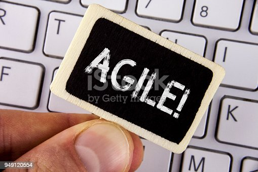 istock Writing note showing  Agile Motivational Call. Business photo showcasing Develop an agility towards technological chnage written on Wood Piece holding by man on the Laptop. 949120554