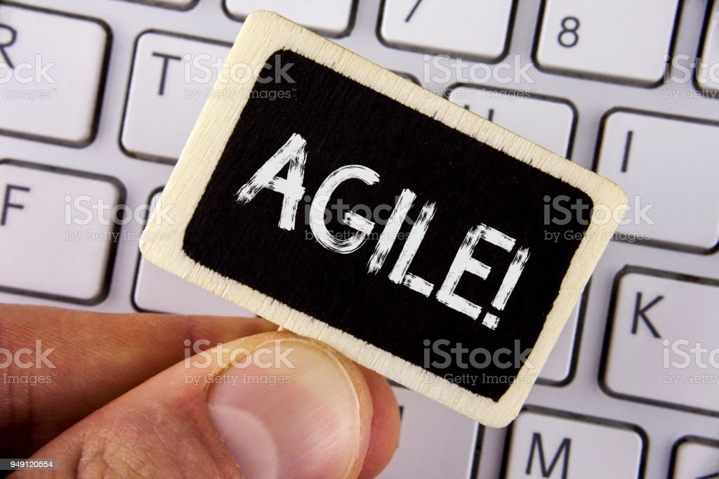 Writing note showing  Agile Motivational Call. Business photo showcasing Develop an agility towards technological chnage written on Wood Piece holding by man on the Laptop. stock photo