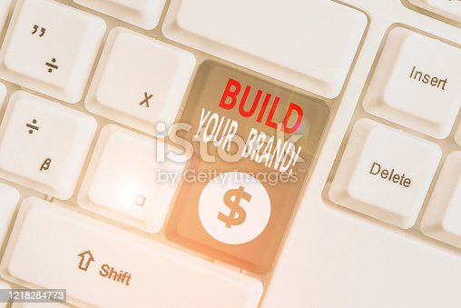 istock Writing note showing Build Your Brand. Business photo showcasing creates or improves customers knowledge and opinions of product White pc keyboard with note paper above the white background. 1218284773