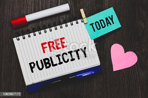 istock Writing note showing Free Publicity. Business photo showcasing Promotional marketing Mass media Public Relations Editorial Open notebook pin holding reminder marker heart wooden background. 1062607172
