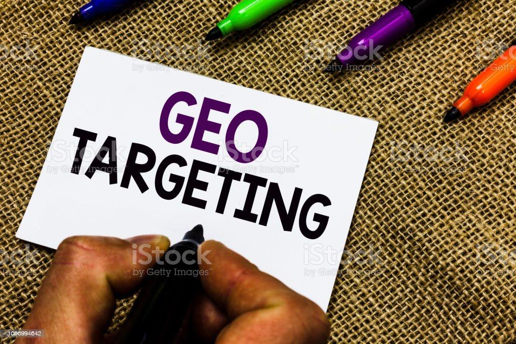 Writing note showing Geo Targeting. Business photo showcasing Digital Ads Views IP Address Adwords Campaigns Location Man hand holding marker white paper communicating idea Jute background. – zdjęcie