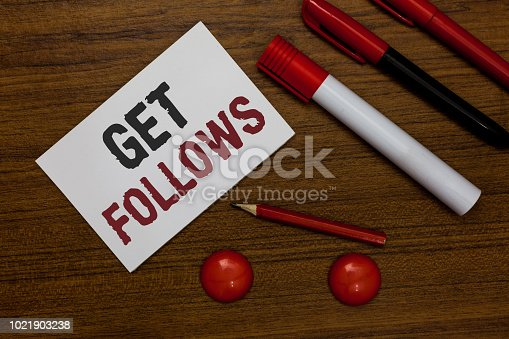istock Writing note showing Get Follows. Business photo showcasing person who imitates copies or takes as model ideal person White paper markers wooden background communicating ideas messages. 1021903238