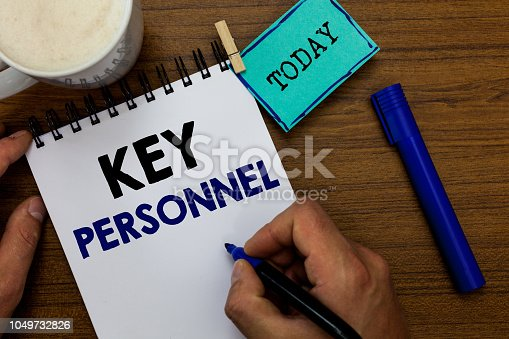 istock Writing note showing Key Personnel. Business photo showcasing Program Directors Principal Investigator Project Executives Man holding marker notebook clothespin reminder wooden table coffee. 1049732826