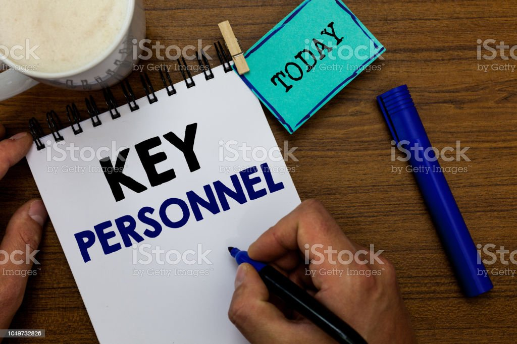 Writing note showing Key Personnel. Business photo showcasing Program Directors Principal Investigator Project Executives Man holding marker notebook clothespin reminder wooden table coffee. stock photo
