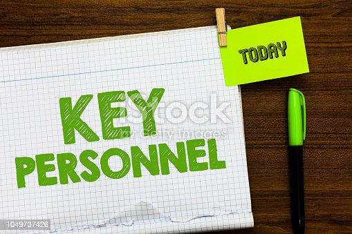 istock Writing note showing Key Personnel. Business photo showcasing Program Directors Principal Investigator Project Executives Open notebook page markers holding paper heart wooden background. 1049737426