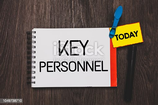 istock Writing note showing Key Personnel. Business photo showcasing Program Directors Principal Investigator Project Executives Open notebook white page clothespin holding reminder wooden background. 1049738710