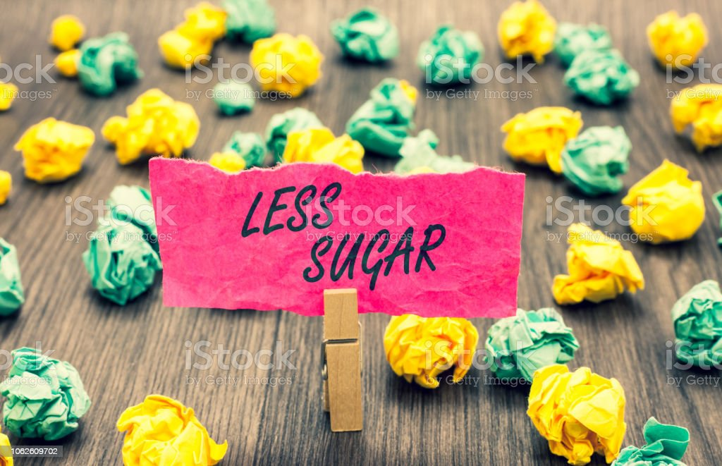 Writing note showing Less Sugar. Business photo showcasing Lower volume of sweetness in any food or drink that we eat Clothespin holding pink note paper crumpled papers several tries. stock photo