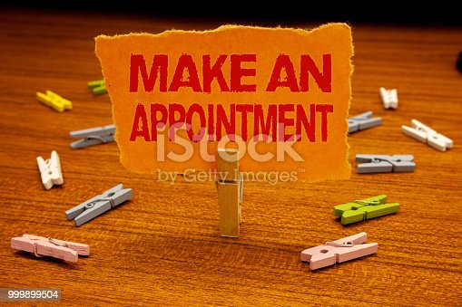istock Writing note showing  Make An Appointment. Business photo showcasing Schedule Arrangement Deadline Session Engagement Paperclip holding orange page show red text woody floor with clip. 999899504