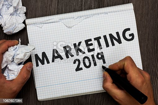 istock Writing note showing Marketing 2019. Business photo showcasing Commercial trends for 2019 New Year promotional event Man holding marker notebook crumpled papers several tries made. 1062607084