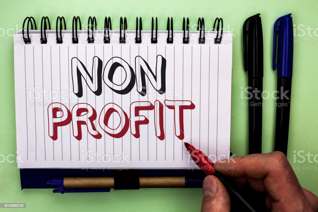 Writing note showing  Non Profit. Business photo showcasing Charitable Wrothless Philanthropy Aid Unlucrative Profitless written by Man Holding Marker on Nootbook Book plain background Marker. stock photo