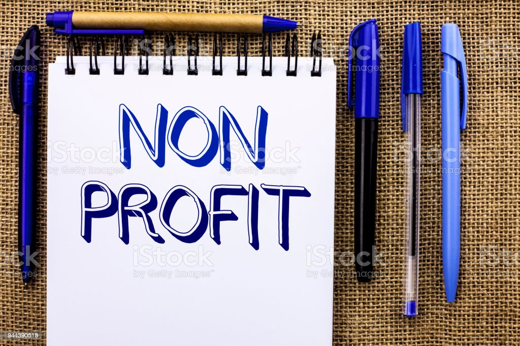 Writing note showing  Non Profit. Business photo showcasing Charitable Wrothless Philanthropy Aid Unlucrative Profitless written on Notebook Book on the jute background Pens next to it. stock photo