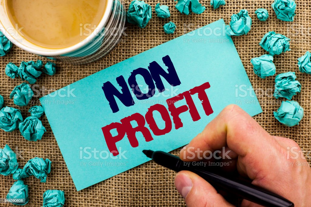Writing note showing  Non Profit. Business photo showcasing Charitable Wrothless Philanthropy Aid Unlucrative Profitless written by Man Holding Pen on Sticky Note Paper the jute background Cup stock photo