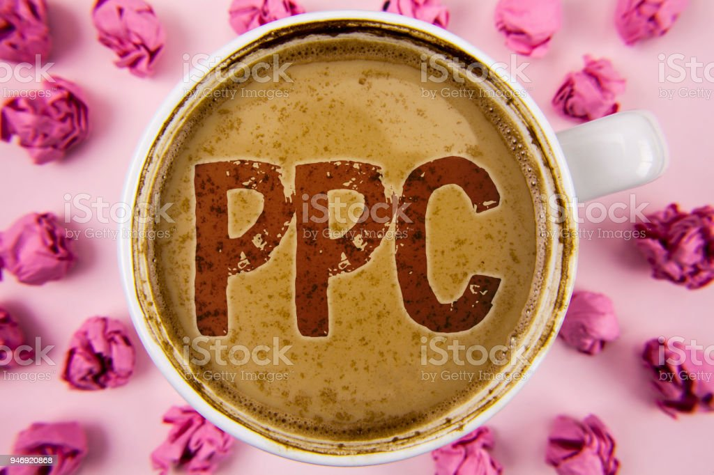 Writing note showing  Ppc. Business photo showcasing Pay Per Click Advertising Strategies Direct Traffic to Websites written on Coffee in white Cup within Paper Balls on plain background. – zdjęcie