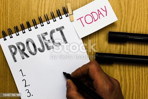 istock Writing note showing Project. Business photo showcasing Planned work activity Study of particular subject Creative job Man holding marker notebook clothepin reminder wooden table cup coffee. 1049736788