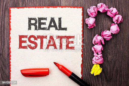 istock Writing note showing  Real Estate. Business photo showcasing Residential Property Building Covered Land Chattels Real written on Cardboard Piece With Marker wooden background Question Mark. 944393734