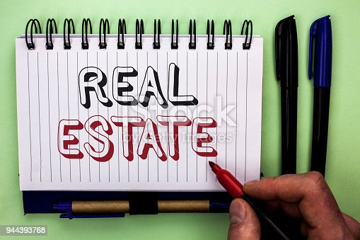 istock Writing note showing  Real Estate. Business photo showcasing Residential Property Building Covered Land Chattels Real written by Man Holding Marker on Nootbook Book plain background Marker. 944393768