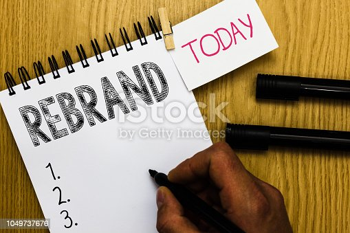 istock Writing note showing Rebrand. Business photo showcasing Change corporate image of company organization Marketing strategy Man holding marker notebook clothepin reminder wooden table cup coffee. 1049737676