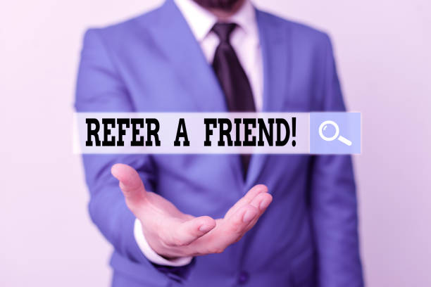 Writing note showing Refer A Friend. Business photo showcasing direct someone to another or send him something like gift Man in front of table. Mobile phone and notes on the table. stock photo