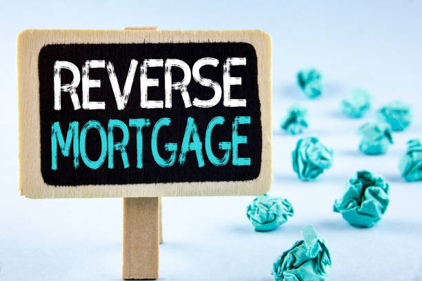 Writing note showing  Reverse Mortgage. Business photo showcasing Elderly homeowner retirement option regular payment benefit written on Wooden Notice Board plain background Paper Balls next to it. stock photo