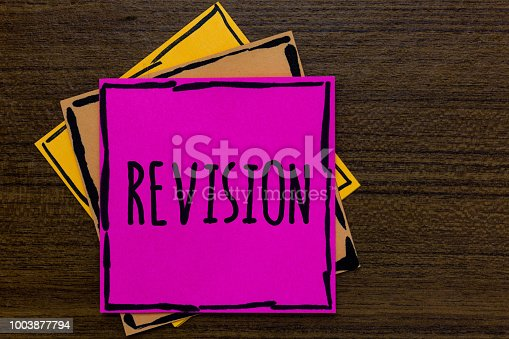 istock Writing note showing Revision. Business photo showcasing Rechecking Before Proceeding Self Improvement Preparation Three art small paper two yellow one pink wood brown lite grey shadow. 1003877794