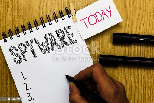 istock Writing note showing Spyware. Business photo showcasing Software that enables user obtain information about other computer Man holding marker notebook clothepin reminder wooden table cup coffee. 1049736980