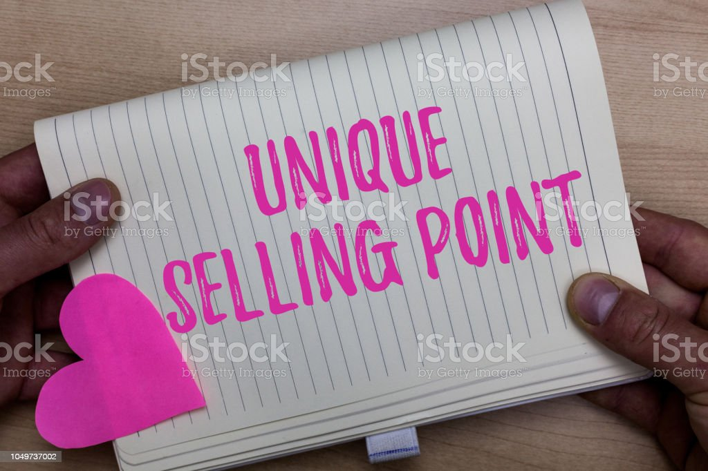 Writing note showing Unique Selling Point. Business photo showcasing Differentiate a Product Specific Features and Benefits Man holding notebook paper heart Romantic ideas Wooden background. stock photo