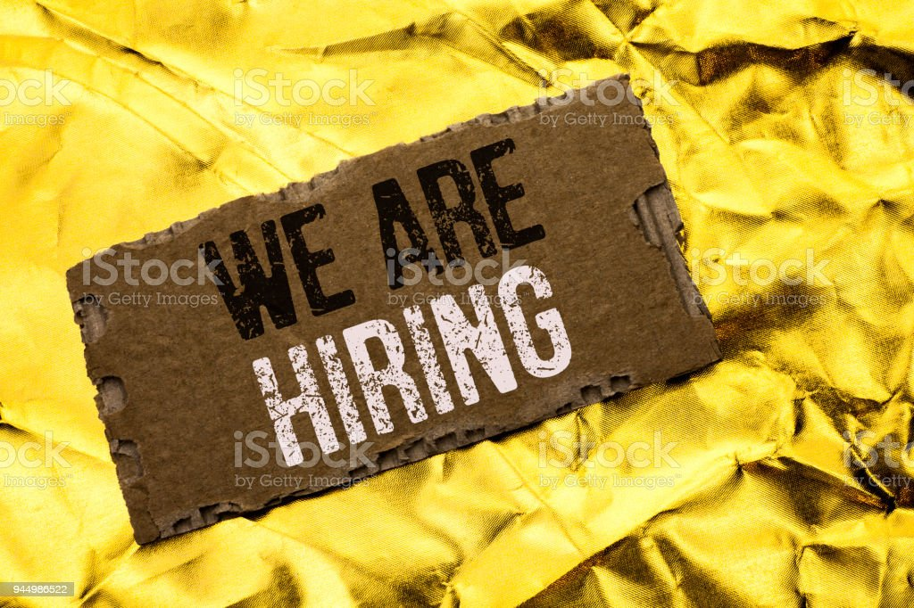 Writing note showing  We Are Hiring. Business photo showcasing Talent Hunting Job Position Wanted Workforce HR Recruitment written on tear Cardboard Piece on the Golden textured background. stock photo