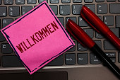 istock Writing note showing Willkommen. Business photo showcasing welcoming people event or your home something to that effect Pink paper keyboard Inspiration communicate ideas messages Red markers. 1046619020