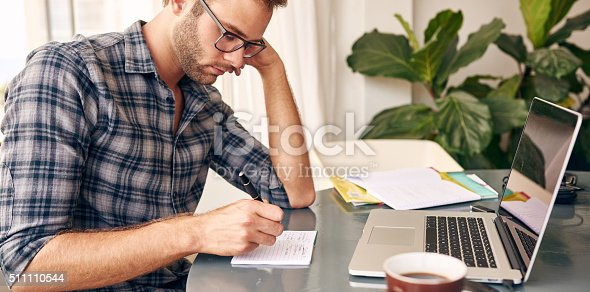 Horizontal image of a businessman writing notes on a writing pad while sitting at his desk behind his new notebook with his morning coffee