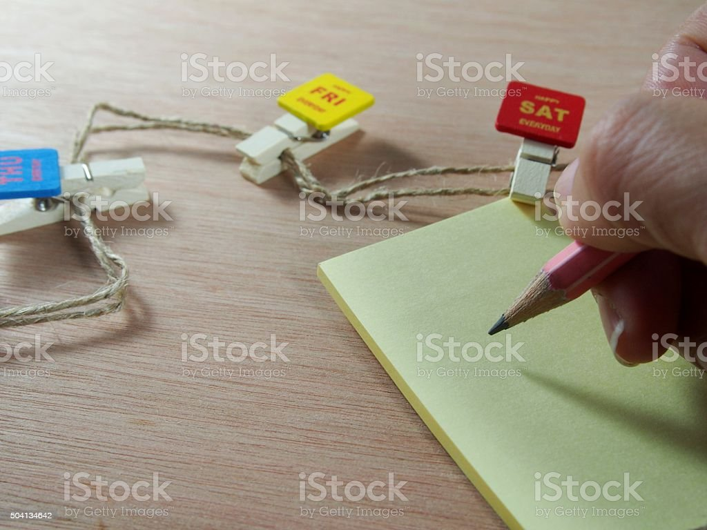 Writing on note paper with wooden paper clips stock photo
