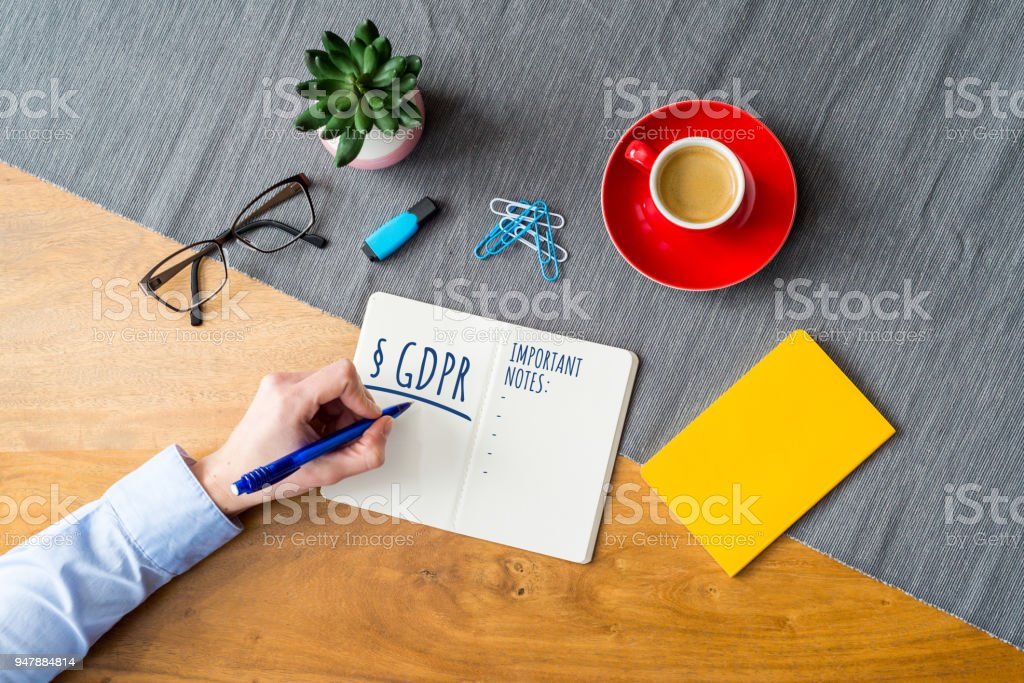 GDPR writing on notebook for data protection regulation as flat lay from above stock photo