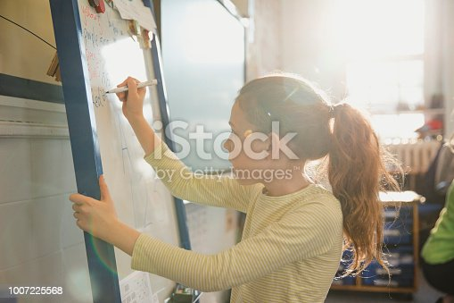 An elementary schoolgirl wearing casual clothing writes on a whiteboard in class. This is a school in Hexham, Northumberland in north eastern England.