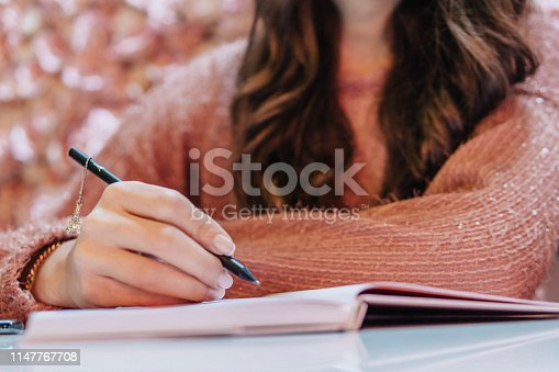 Young woman handwriting on her diary. Pink roses on the background