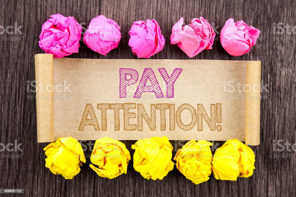 Writing text  Pay Attention. Concept meaning Be Careful Beware Mindful Alarm written on sticky note paper with folded paper yellow and pink on the wooden background. stock photo