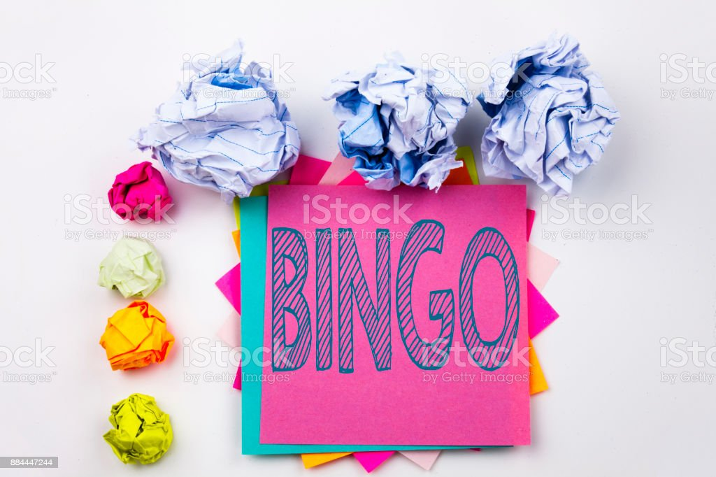 Writing text showing Bingo written on sticky note in office with screw paper balls. Business concept for Lettering Gambling to Win Price Success on the white isolated background. stock photo
