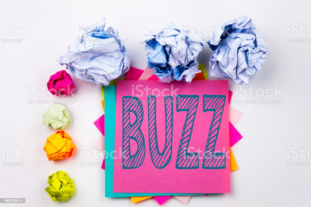 Writing text showing Buzz written on sticky note in office with screw paper balls. Business concept for Buzz Word llustration on the white isolated background. stock photo