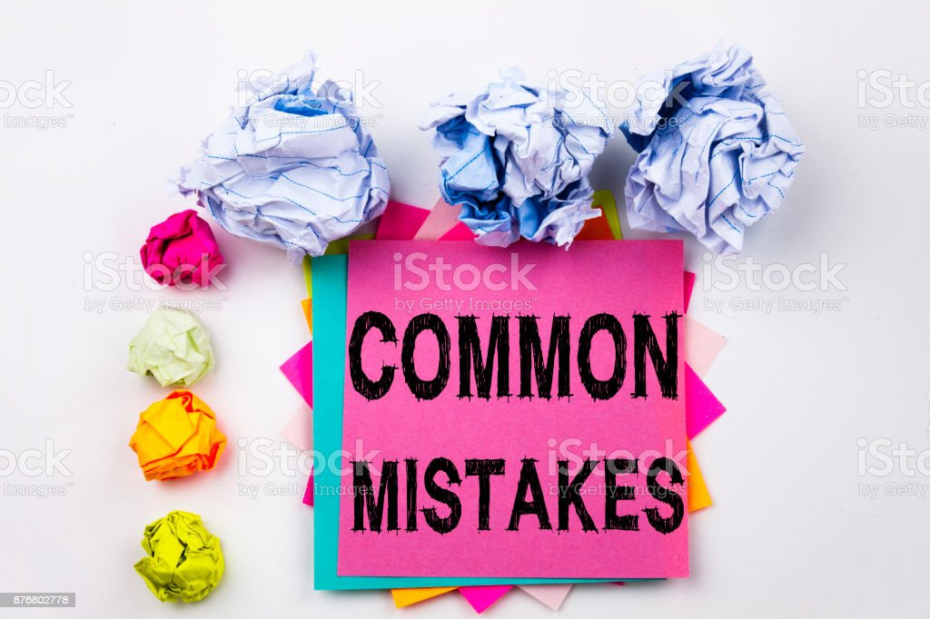 Writing text showing Common Mistakes written on sticky note in office with screw paper balls. Business concept for Common Decision Mistakes on the white isolated background. stock photo