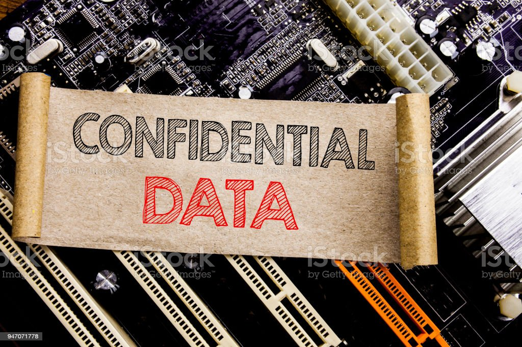 Writing text showing Confidential Data. Business concept for Secret Protection Written on sticky note, computer main board background. stock photo